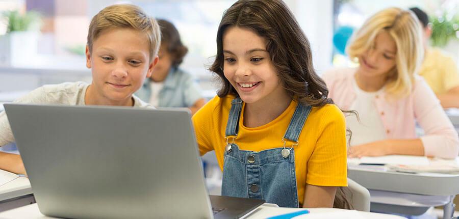 Zwei Kinder vor Computer programmieren gemeinsam
