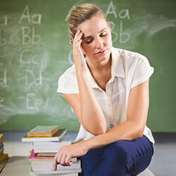 Lehrerin vor Tafel guckt verzweifelt