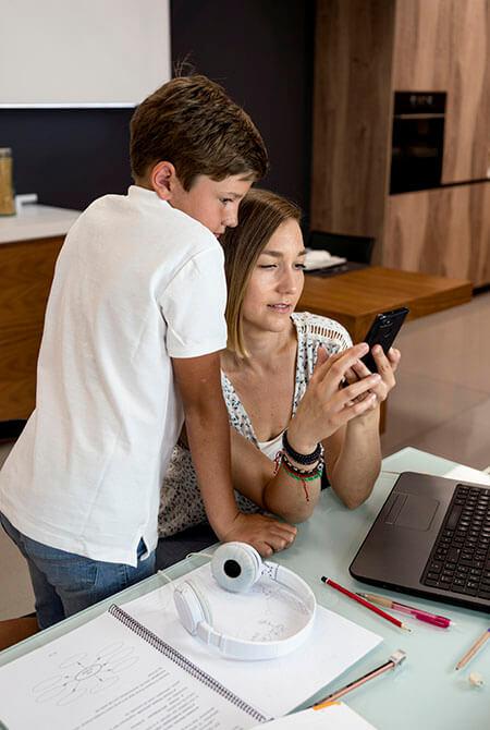 Mutter zeigt Sohn etwas auf Smartphone