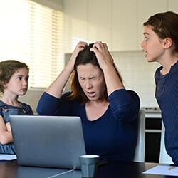 Mutter verzweifelt vor Kindern am Computer