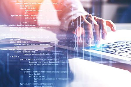 Codezeilen vor Mitarbeiter an Computer