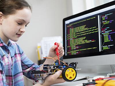Schülerin programmiert Roboter vor Computer