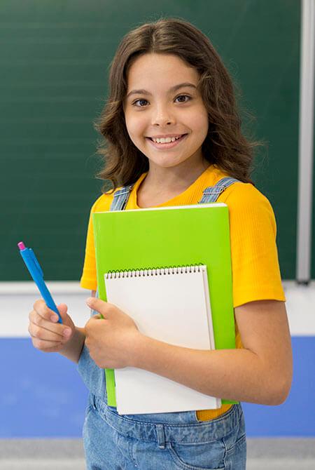 Glückliche Schülerin steht vor einer Tafel
